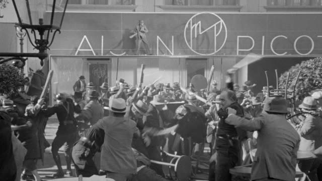MS Shot of people rioting in street in front of Maison Pico and one man to breaking of Maison Pico name