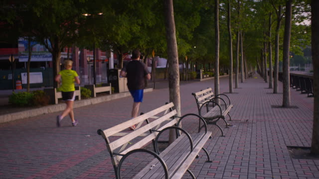 Shot of people running along a path near the Hudson River in Hoboken