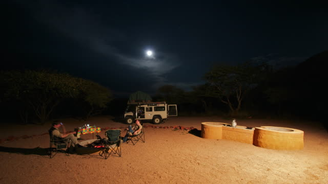 vídeos y material grabado en eventos de stock de ms t/l shot of people set up camp in desert as full moon rises in night sky, camp fire is lit, cooking, eating and organisation / okonjima, windhoek, namibia - 4x4