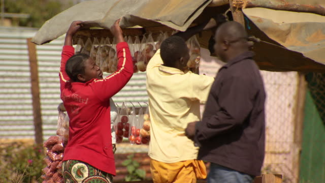 vídeos y material grabado en eventos de stock de ms shot of people setting up fruit stall / durban south africa - kwazulu natal
