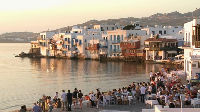 ws shot of people sitting at little venice restaurant / mykonos, cyclades, greece - mykonos stock videos and b-roll footage