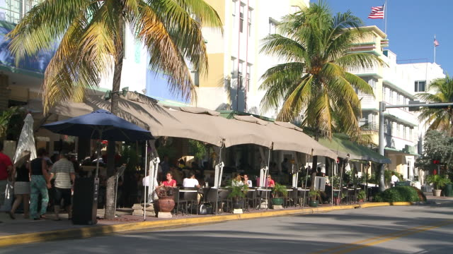MS Shot of People sitting in café on Ocean Drive with people walking / Miami Beach, Florida, United States