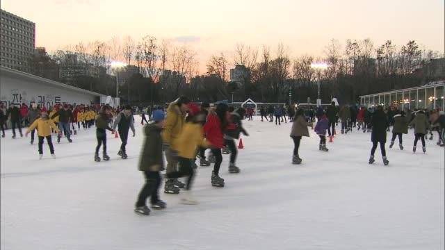 vídeos y material grabado en eventos de stock de shot of people skating at seoul city hall plaza - plaza