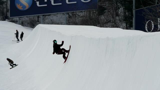 shot of people snowboarding on halfpipe at ski resort - half pipe stock videos & royalty-free footage