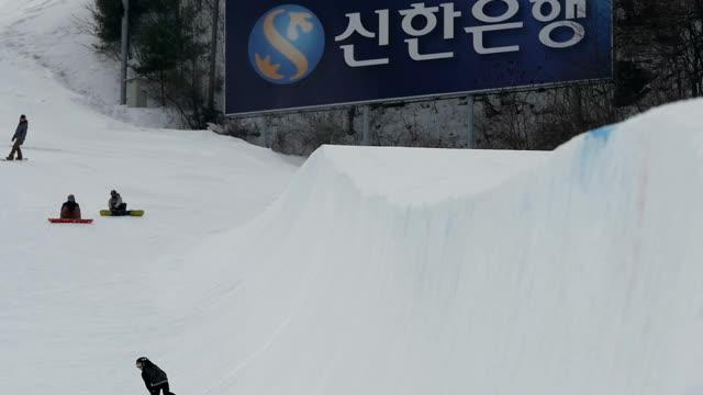 shot of people snowboarding on halfpipe at ski resort - halfpipe stock-videos und b-roll-filmmaterial