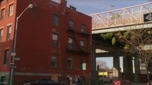 A POV shot of people standing on sidewalks in Brooklyn near the Williamsburg Bridge in New York City.
