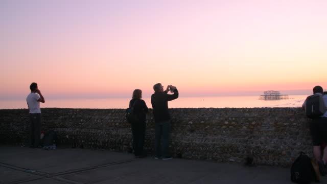 shot of people taking photographs from the seawall on brighton beach at sunset. - イーストサセックス点の映像素材/bロール