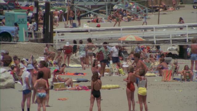 stockvideo's en b-roll-footage met ms pan shot of people taking sun bath on crowded beach - zonwering