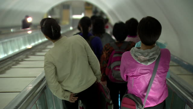 pov shot of people travelling down an escalator in a subway station in pyongyang - pyongyang stock videos and b-roll footage