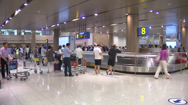Shot of people waiting luggage at baggage claim area in Incheon International Airport