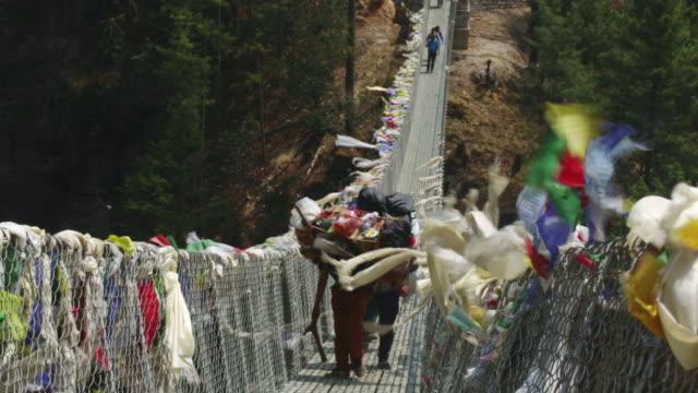 MS Shot of people walking across suspension bridge at Larjha Doban remote Mt Everest / SoluKhumbu, Nepal