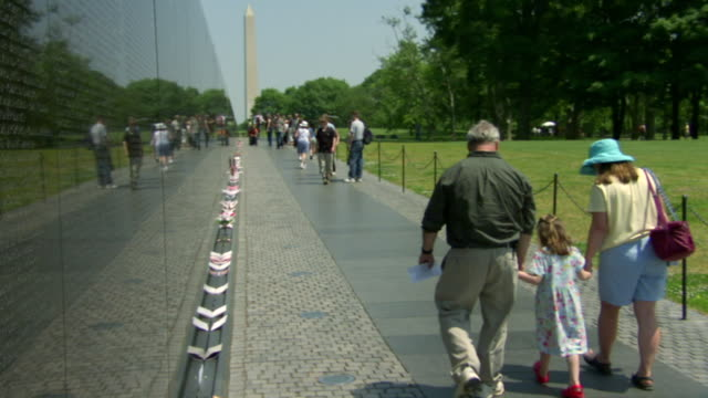 MS Shot of people walking alongside of Vietnam Veterans Memorial wall with Washington Monument / Washington, District of Columbia, United States