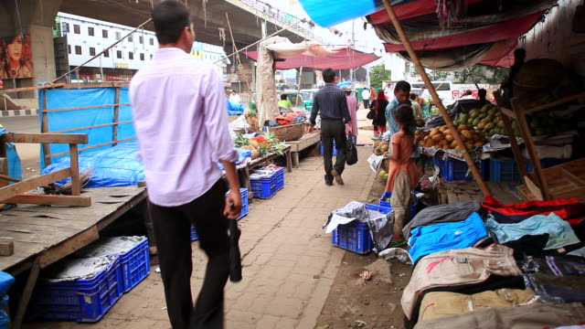 WS Shot of people walking among street vendors selling fruit and clothes on busy street / Dhaka, Bangladesh