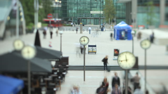 ms t/l shot of people walking and clocks in canary wharf / london, greater london, united kingdom - tilt shift stock videos and b-roll footage