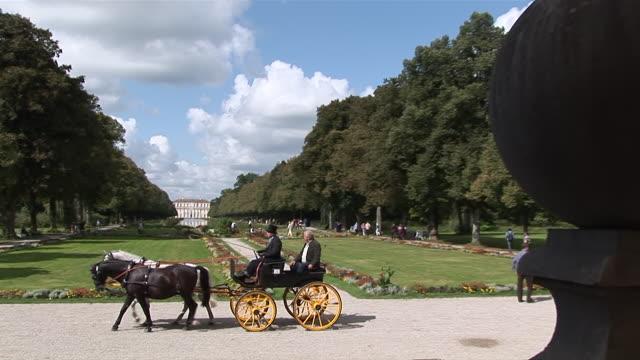 ms pan zi shot of people walking and  horse coach passing through garden of schleiãŸheim castle / munich, bavaria, germany - arbeitstier stock-videos und b-roll-filmmaterial