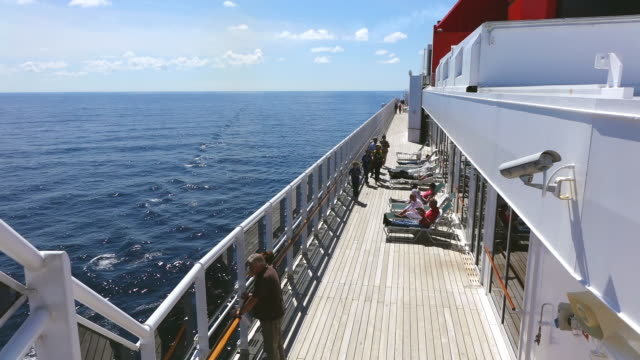 MS Shot of People walking and standing on board cruise ship Queen Mary 2, Cunard Line / North Sea, Jutland, Denmark