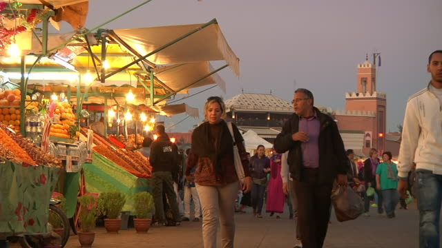 MS Shot of people walking around dusk near market stands in downtown / Fes, Centro-North, Morocco