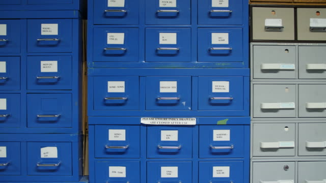 stockvideo's en b-roll-footage met shot of people walking by a blue filing cabinet containing index cards - bbc archives