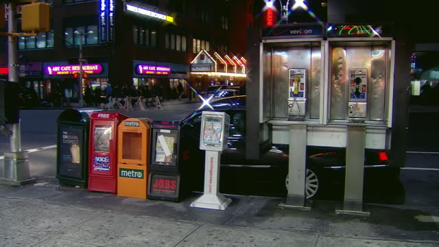 MS Shot of People walking by pay phones at street intersection at night / New York, United States