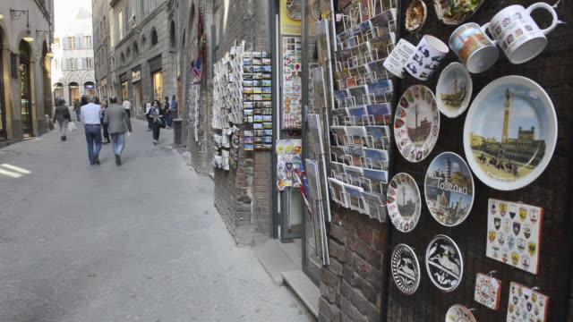 ms shot of people walking in old town lane / siena, tuscany, italy - ギフトショップ点の映像素材/bロール