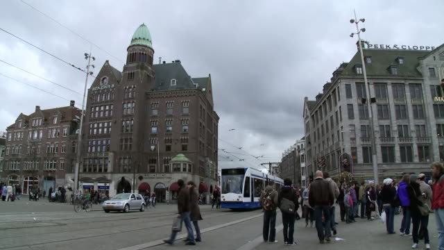 MS Shot of People walking in town square, historic buildings in back side to tram moving along road / Amsterdam, Holland