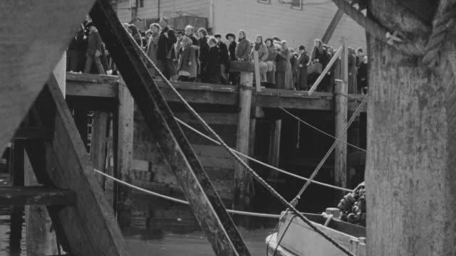 MS LA Shot of people walking on dock to entering in boat