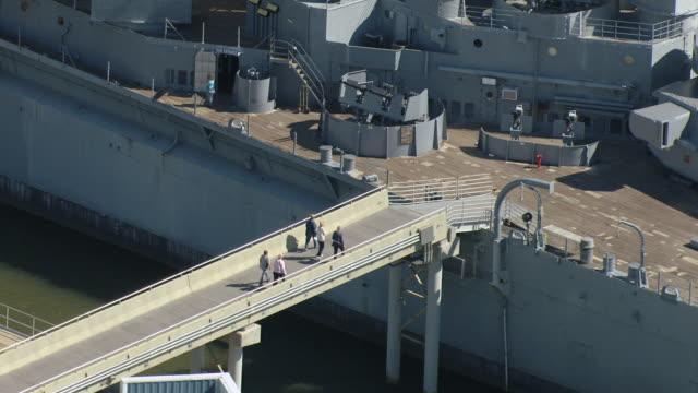 MS AERIAL ZO Shot of people walking on plank to USS Alabama ship / Alabama, United States