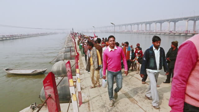 ms shot of people walking on pontoon bridge over gangas river during kumbh mela / allahabad, uttar pradesh, india - pontoon bridge stock videos and b-roll footage