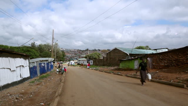 ws shot of people walking on street with huge slum / nairobi, kenya - remote location stock videos & royalty-free footage