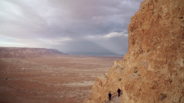 ws shot of people walking pathway on masada and desert in distance with ray of light penetrating through clouds in sky / israel - biblical event stock videos & royalty-free footage
