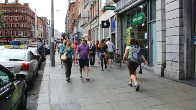 vídeos y material grabado en eventos de stock de ms shot of people walking through city streets / dublin, dublin region, ireland - escritura occidental