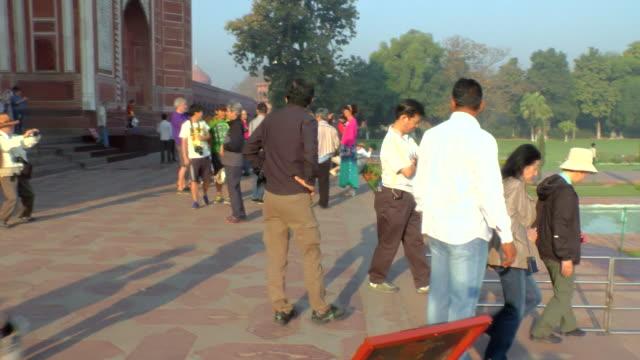 ms pan shot of people walkway next to reflecting pool in front of taj mahal / agra, uttar pradesh, india - agra video stock e b–roll