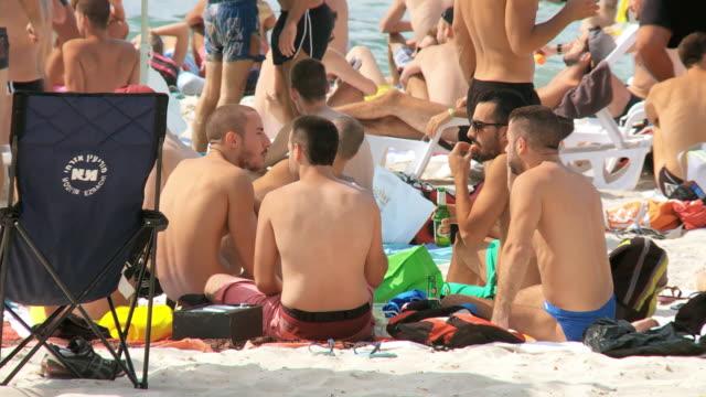ms shot of people with bathing suits having fun on sunny day / tel aviv, dan metropolitan,gush dan, israel - 胡坐点の映像素材/bロール