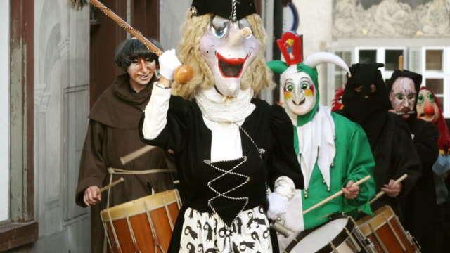 ms shot of people with mask and dressing up playing drums at celebrating basler fasnacht (basel carnival) on street / basel, switzerland - kostümierung stock-videos und b-roll-filmmaterial