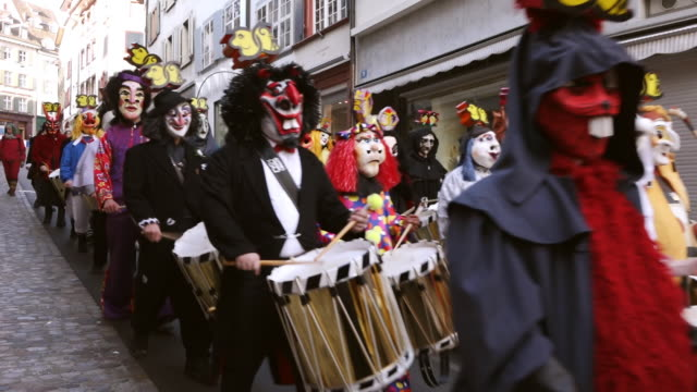 ws shot of people with mask and dressing up playing flute and drums at celebrating basler fasnacht (basel carnival) on street / basel, switzerland - animal imitation stock videos and b-roll footage