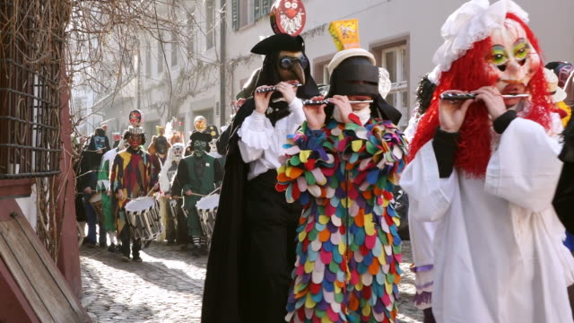ms shot of people with mask and dressing up playing flute and drums at celebrating basler fasnacht (basel carnival) on street / basel, switzerland - fasching stock-videos und b-roll-filmmaterial