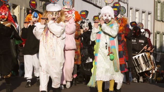 ms shot of people with mask and dressing up playing flute celebrating basler fasnacht (basel carnival) on street / basel, switzerland - animal imitation stock videos and b-roll footage