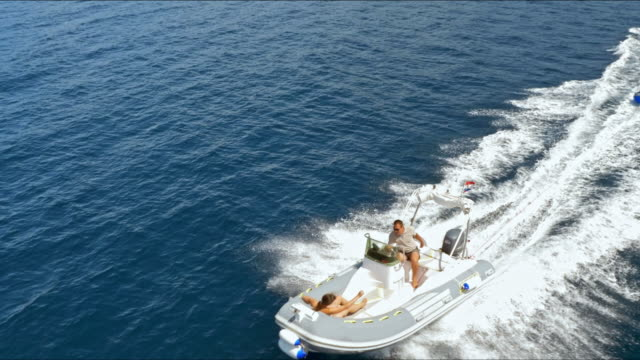 aerial shot of person being towed on an inflatable tube - towing stock videos and b-roll footage