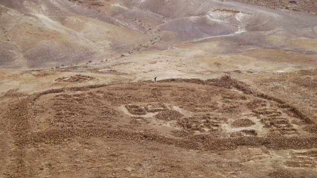 ws shot of person standing in remnants of siege wall and fortress at masada in negev desert / israel - fortress stock videos and b-roll footage