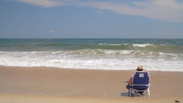 vídeos de stock, filmes e b-roll de ws shot of person wearing large sun hat seating on beach and waves crashing / rodanthe, north carolina, united states - câmara parada