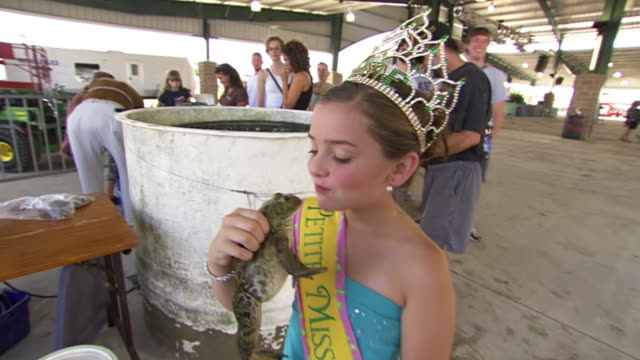 vídeos de stock, filmes e b-roll de ms zi shot of petite miss rayne kissing bullfrog during rayne frog festival / rayne, louisiana, united states - contestant