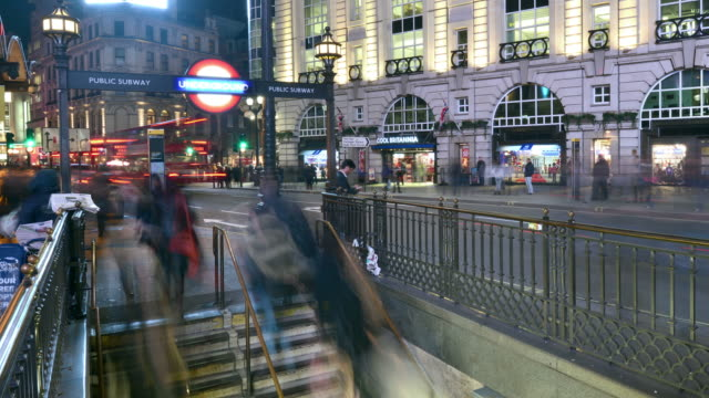 stockvideo's en b-roll-footage met ms zo t/l shot of piccadilly circus underground entrance night wide commuters enter and exit on steps traffic and shops restaurants in back side / london, greater london, united kingdom - greater london