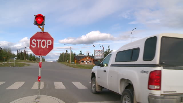 cu shot of pickup turns left from yukon 1 onto haines highway / haines junction, yukon, canada - stop sign stock videos & royalty-free footage