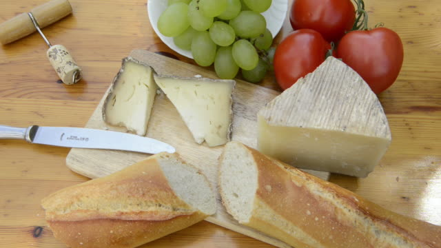 ms shot of picnic with cheese, bread, tomatoes and grapes / siena, tuscany, italy - チーズ点の映像素材/bロール