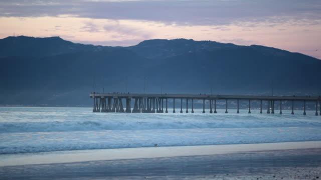 vídeos y material grabado en eventos de stock de ws shot of pier between ocean and mountains at sunset / los angeles, california, united states - grupo pequeño de animales