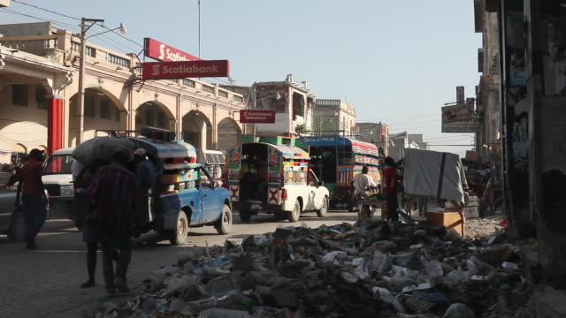 MS Shot of Piles of garbage sit alongSide street busy with traffic / Port-au-Prince, Haiti