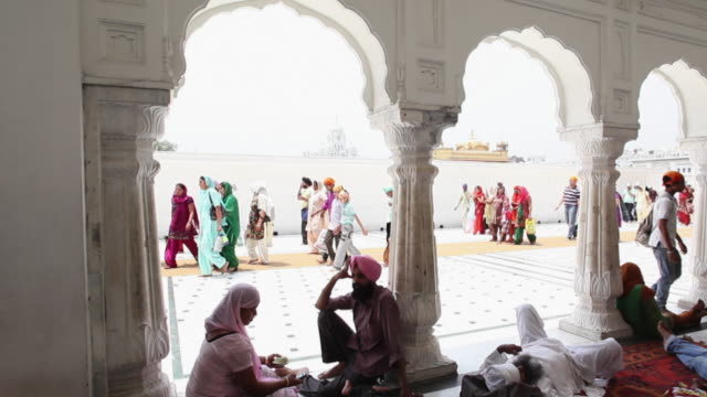 MS PAN Shot of pilgrims in courtyard and corridor of Golden Temple / Amritsar, Punjab, India