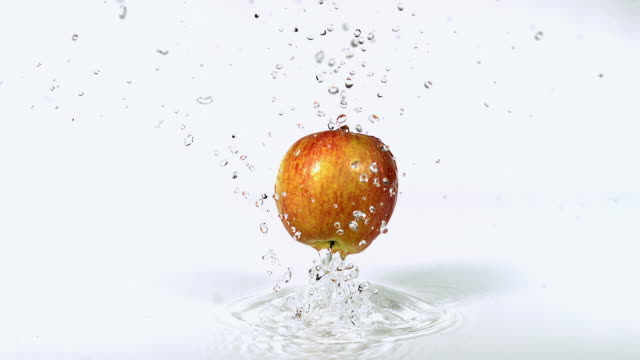 CU SLO MO Shot of Pink Lady Apple, malus domestica, Fruit falling on Water against White Background / Calvados, Normandy, France