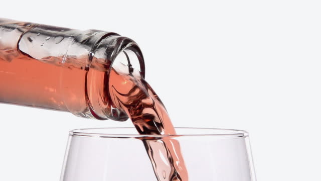 cu slo mo shot of pink wine being pour into glass against white background / calvados, normandy, france - pouring stock videos & royalty-free footage
