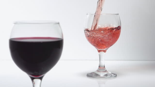 cu slo mo shot of pink wine being pour into glass against white background / calvados, normandy, france - rose wine stock videos and b-roll footage